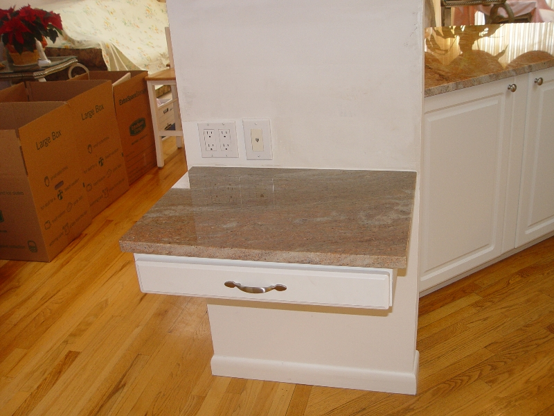 little built in shelf with a drawer and a granite slab countertop