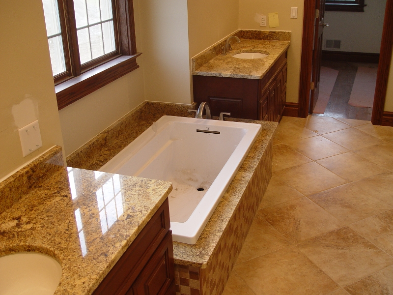 granite counter top and tub ledge in a new bathroom